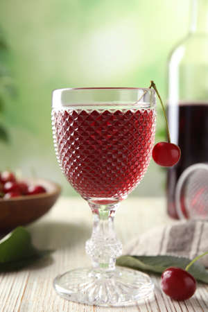 Delicious cherry wine with ripe juicy berries on white wooden table