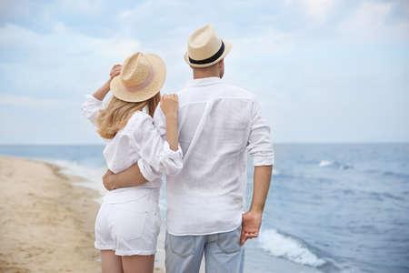 Happy couple having romantic walk on beach