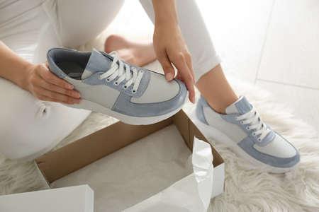 Woman measuring new stylish sneakers indoors, closeup Stock fotó