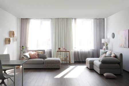 Elegant living room with comfortable sofas near windows. Interior design Banque d'images