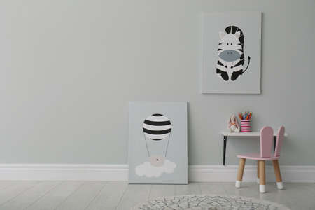Stylish child's room interior with adorable paintings, small table and chair. Space for text