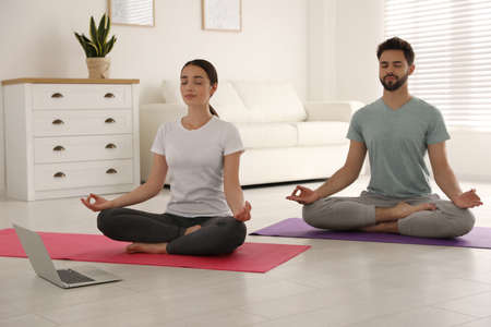 Couple practicing yoga while watching online class at home during coronavirus pandemic. Social distancing