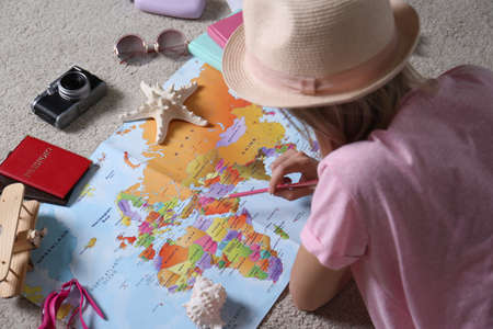 Woman with world map planning trip at home, closeup. Summer vacation Standard-Bild