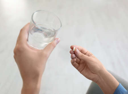 Woman holding glass of water and pill at home, closeup