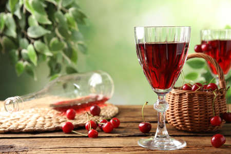 Delicious cherry wine and ripe juicy berries on wooden table. Space for text