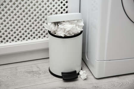 Used paper tissues in trash can near washing machine indoors