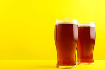 Delicious homemade kvass in glasses on yellow background. Space for text