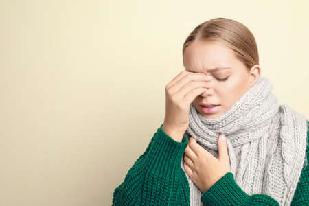 Young woman wearing scarf suffering from headache on light background, space for text. Cold symptoms