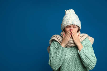 Young woman wearing hat and scarf sneezing on blue background, space for text. Cold symptoms
