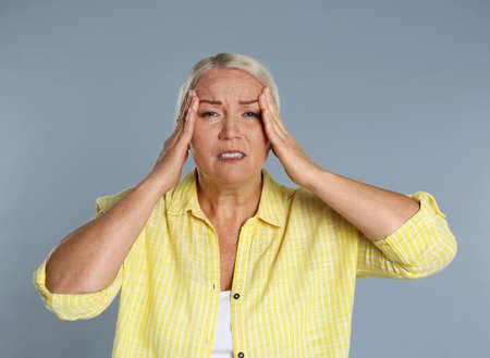 Mature woman suffering from headache on gray background