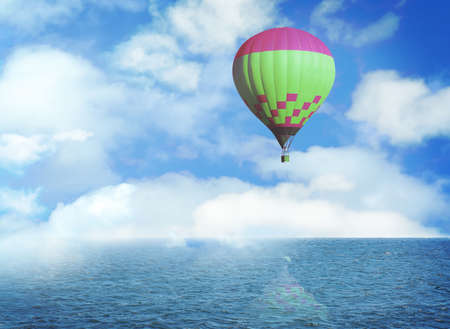 Dream world. Hot air balloon in blue sky with clouds over sea Stock fotó