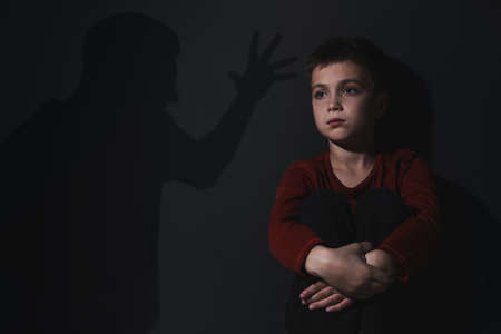 Child abuse. Father yelling at his son. Shadow of man on wall