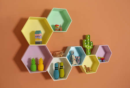 Hexagon shaped shelves with toys on orange wall. Interior design