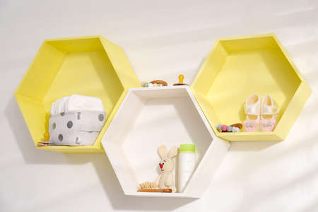 Hexagon shaped shelves with toys and child's accessories on white wall. Interior design