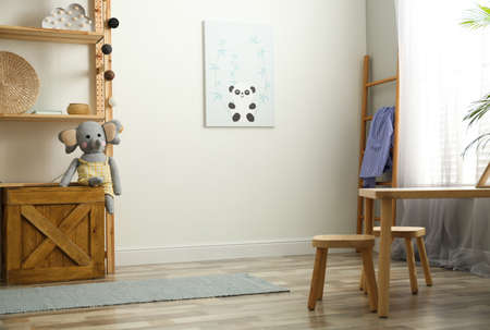 Cute picture on white wall and wooden furniture indoors. Children's room interior design Stock fotó