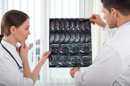 Orthopedists examining X-ray picture near window in office