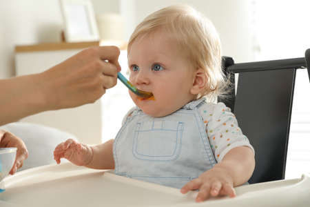 Mother feeding her cute little baby with healthy food at home