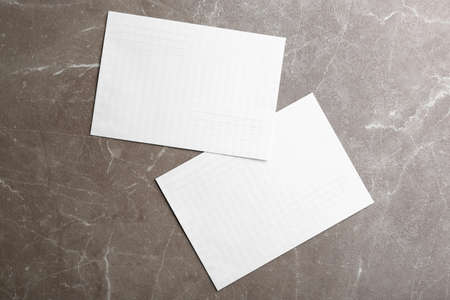 White paper envelopes on marble background, flat lay