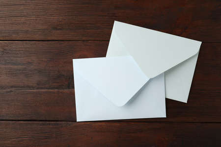 White paper envelopes on wooden table, top view
