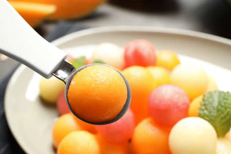 Scoop with melon ball near plate of fruit salad, closeup