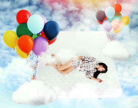 Sweet dreams. Bright cloudy sky with air balloons around sleeping young woman