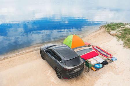 Car and camping equipment on sandy beach. Summer trip
