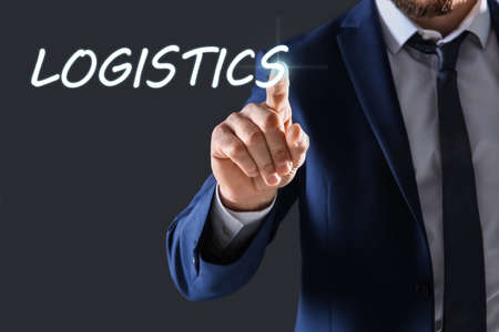 Businessman pointing at word LOGISTICS on virtual screen against dark background, closeup