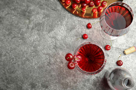 Delicious cherry wine with ripe juicy berries on gray table, flat lay. Space for text