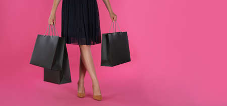 Woman with shopping bags on pink background, closeup. Black Friday Sale Stock fotó