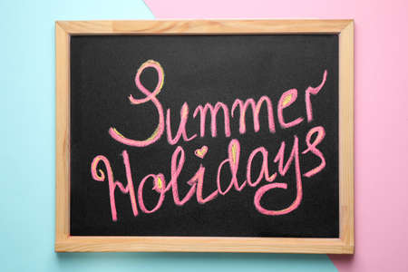 Chalkboard with phrase SUMMER HOLIDAYS on color background, top view. School's out