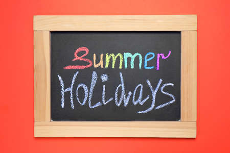 Chalkboard with phrase SUMMER HOLIDAYS on coral background, top view. School's out