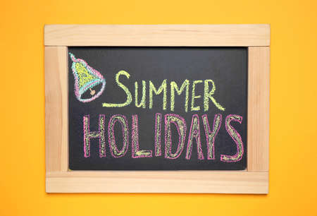 Chalkboard with phrase SUMMER HOLIDAYS on orange background, top view. School's out