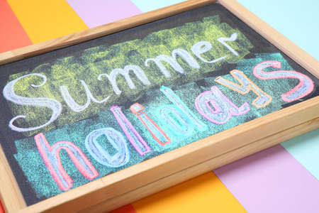 Chalkboard with phrase SUMMER HOLIDAYS on color background, closeup. School's out