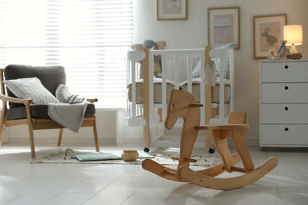 Wooden rocking horse in baby room interior. Idea for design