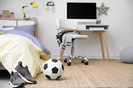 Soccer ball and sneakers near bed in teenager's room interior