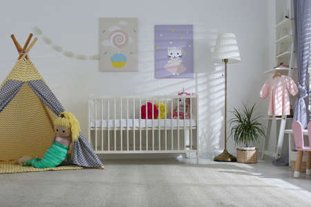 Baby room interior with cute posters, play tent and comfortable crib