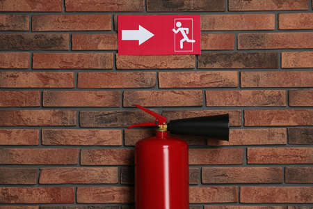 Fire extinguisher and emergency exit sign on brick wall indoors