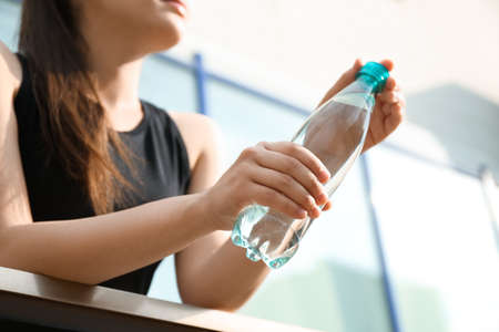 Young woman with bottle of pure water outdoors, closeup