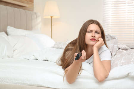 Lazy young woman watching TV in bedroom