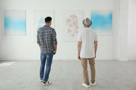 Men at exhibition in art gallery, back view Stock Photo