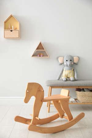 Wooden rocking horse in cute children's room interior. Stylish design