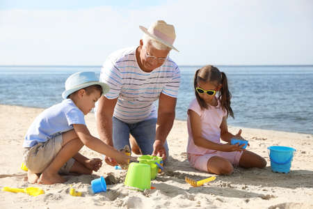 Little children and grandfather playing with plastic toys on sea beach Stockfoto