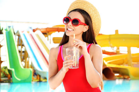 Woman with glass of refreshing drink in water park Stock fotó
