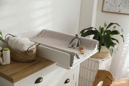 Chest of drawers with changing pad and tray in nursery. Baby room interior design