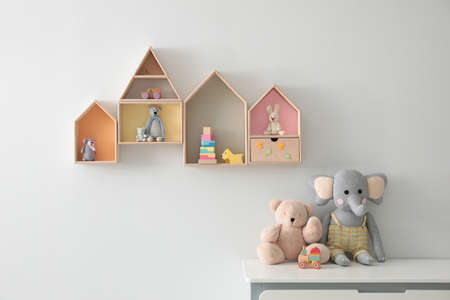 House shaped shelves and chest of drawers with toys in children's room. Interior design