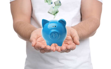 Young man and Euro banknotes falling into piggy bank on white background, closeup