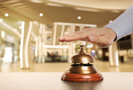 Man ringing hotel service bell on blurred background, closeup