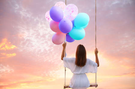 Dream world. Young woman with bright balloons swinging, sunset sky on background