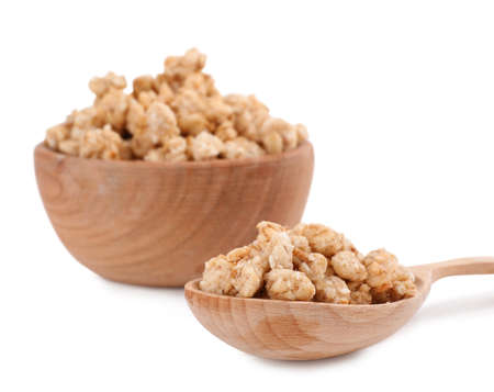 Tasty crispy granola in wooden bowl and spoon on white background Imagens