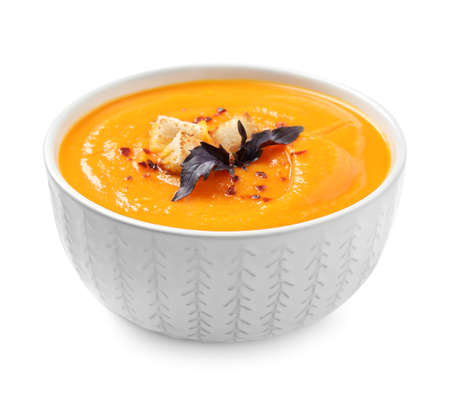 Tasty creamy pumpkin soup in bowl on white background Foto de archivo